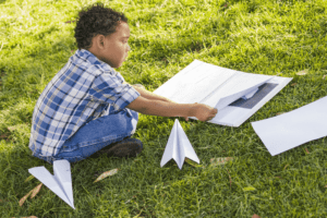 boy learning to fly paper airplanes at airshow