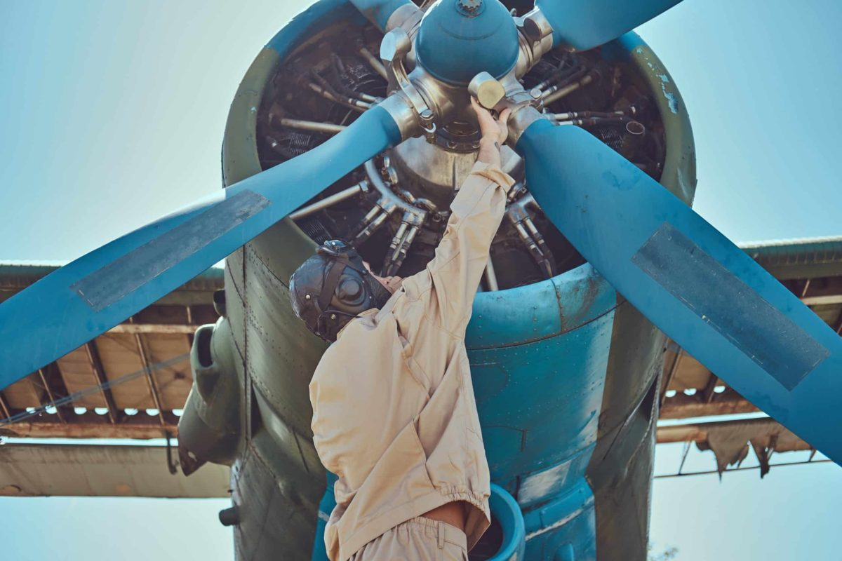 Pilot in vintage flight gear checking propeller of his retro aircraft