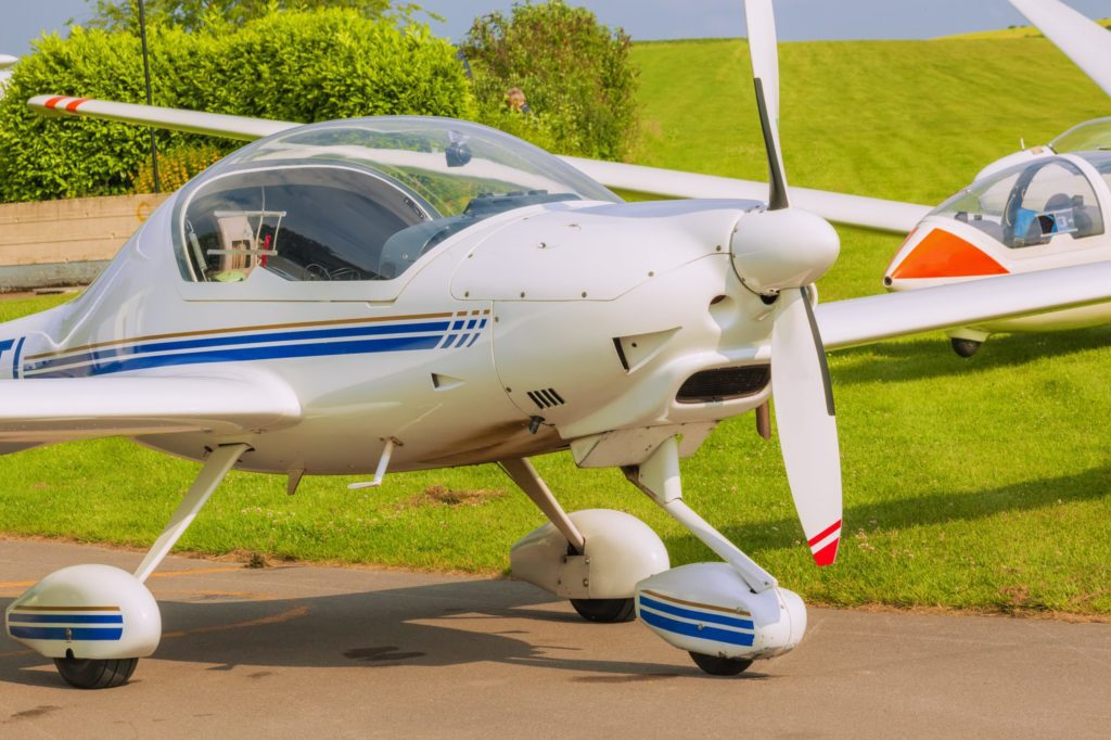 Ultralight Airplane with green grass and trees in background