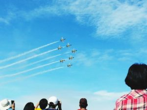 People on the ground, looking up, watching 8 planes flying in formation
