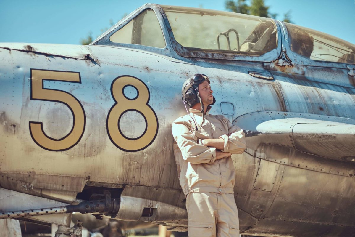 Mechanic in uniform and flying helmet standing near an old war fighter