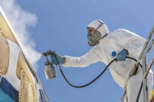Technician in Tyvek and respirator painting aircraft