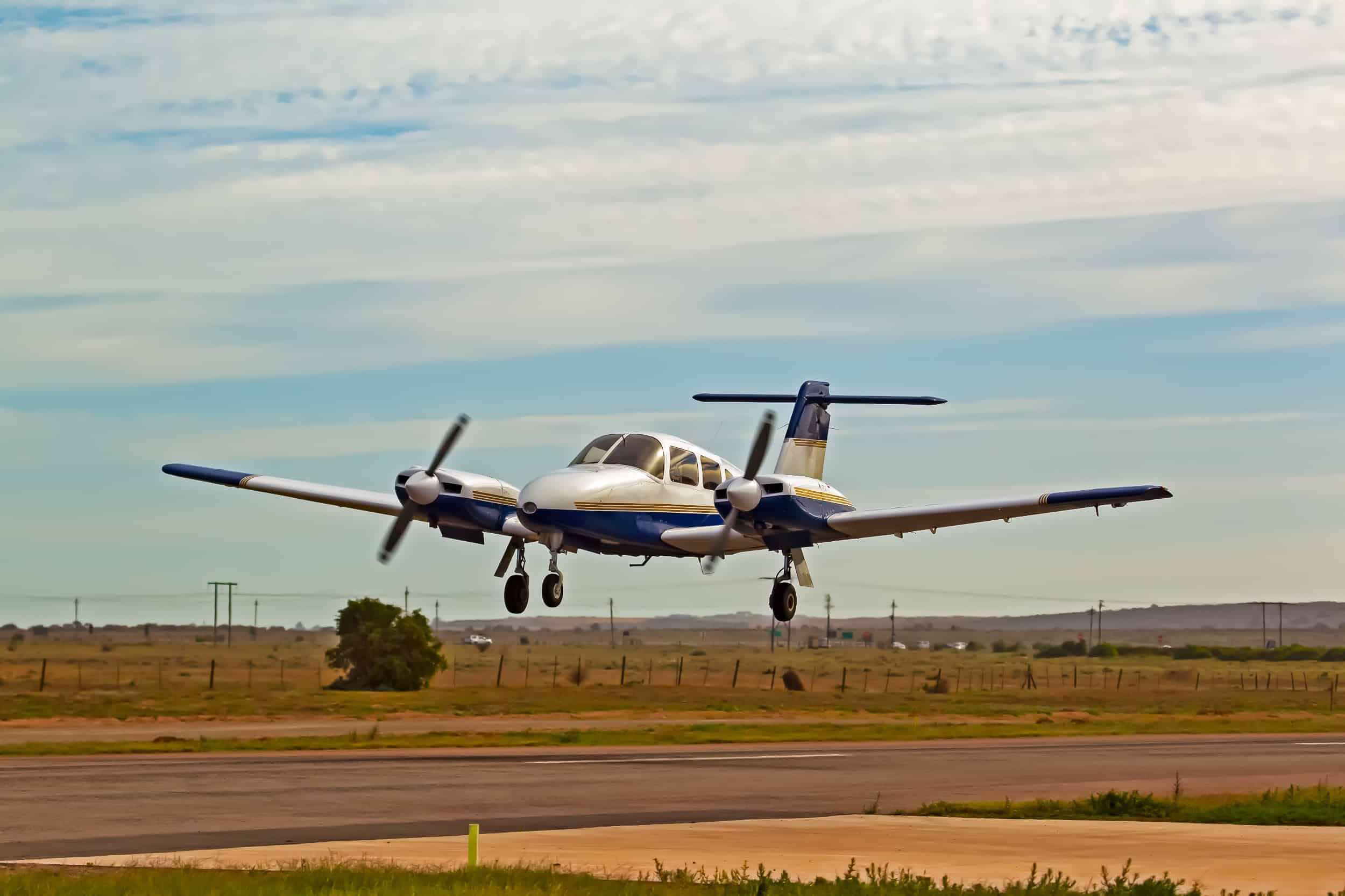 Twin blade propeller plane landing on a runway