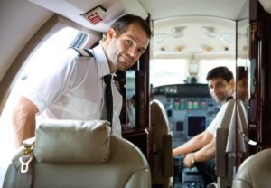 Pilot entering the cabin of a private plane with another pilot and the cockpit in the background