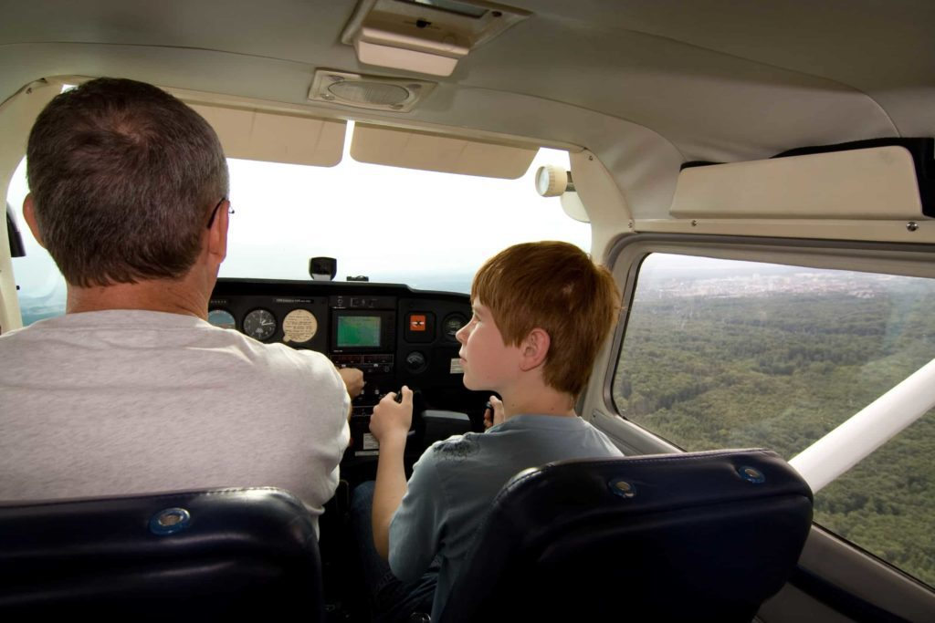Father and son in the cockpit of a small plane flying