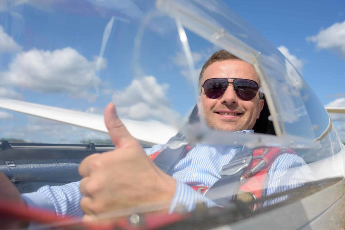 gentleman giving a thumbs up sign through a clear canopy on a small glider