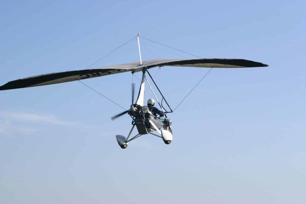 ultralight aircraft taking off against a blue sky