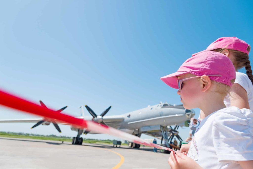 Two young girls behinda safety tape on a tarmac at an airshow with a propeller plane in the background